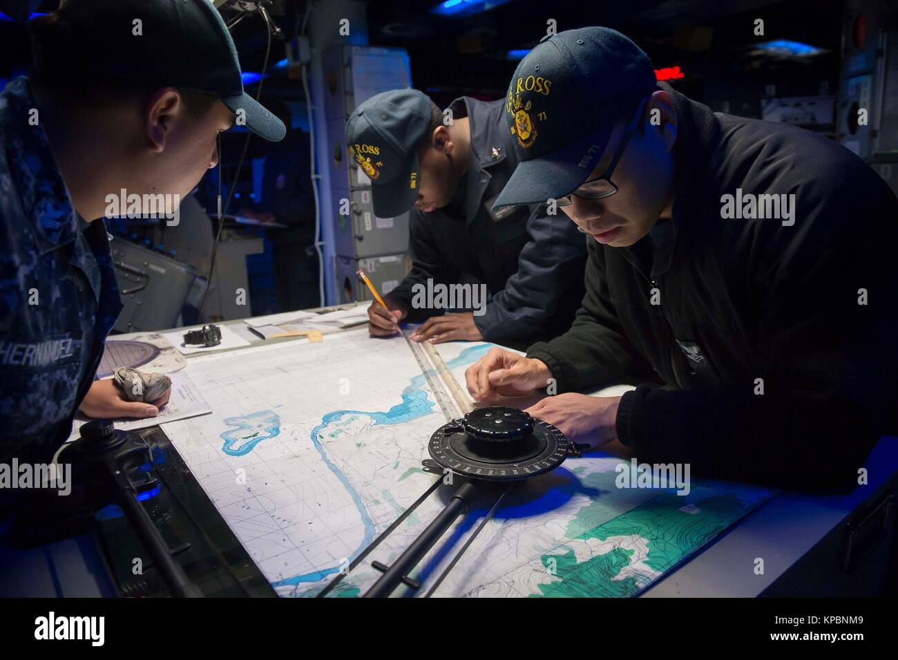 U.S. Navy sailors aboard the U.S. Navy Arleigh Burke-class guided-missile destroyer USS Ross work on plotting and - Stock Image