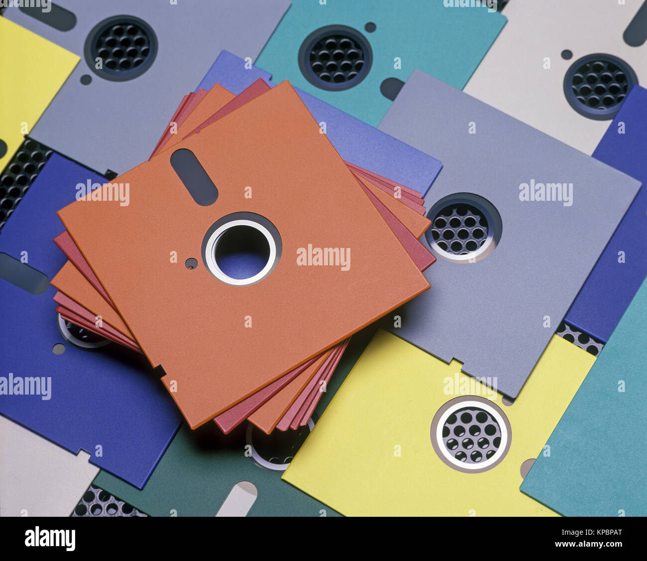 1989 HISTORICAL STACK OF 5.25 INCH MULTICOLORED FLOPPY COMPUTER DISCS ON BLACK METAL SURFACE (©IBM 1973) - Stock Image