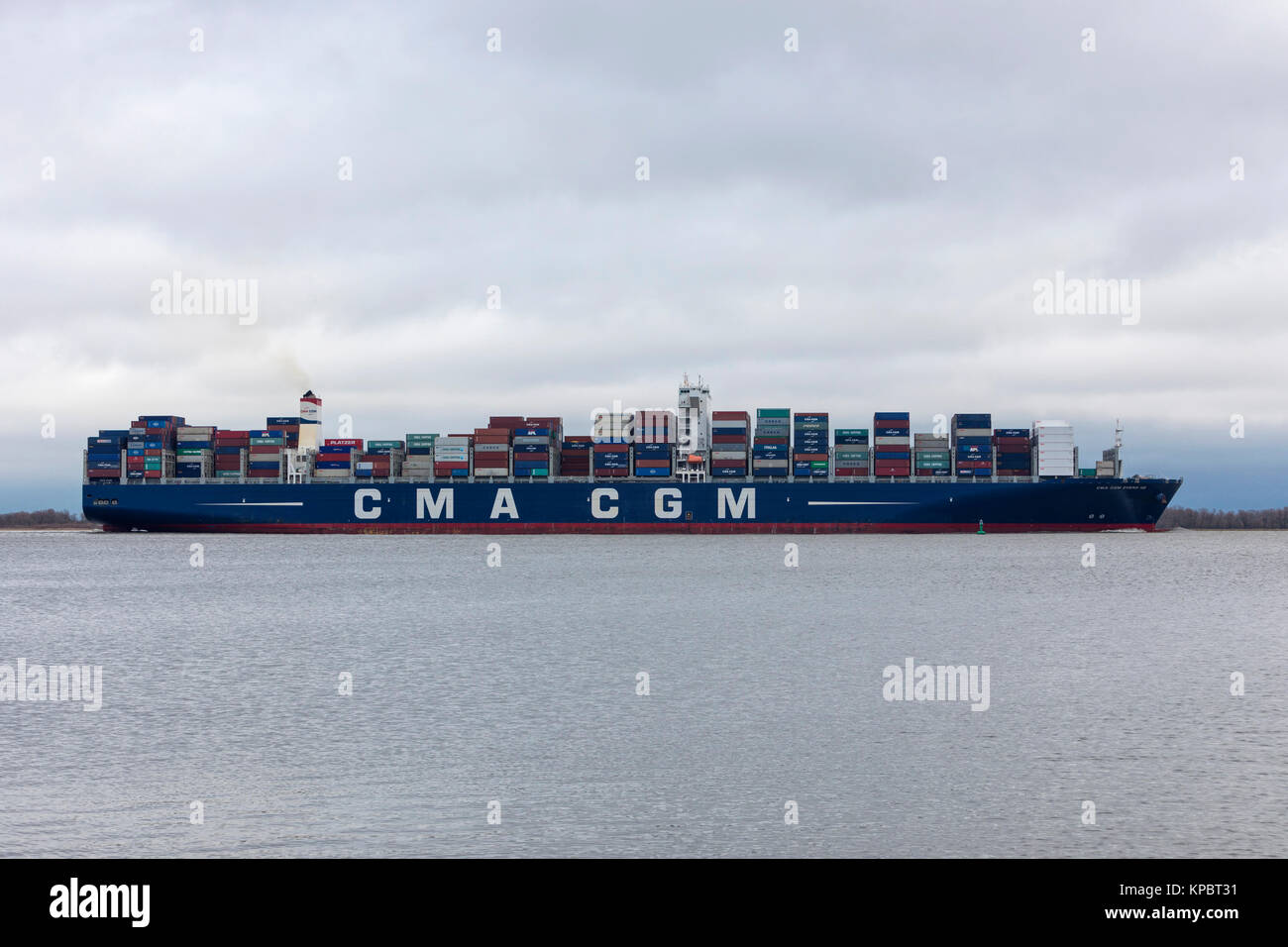 Hollern, Germany - December 14, 2017: Container ship CMA CGM ZHENG HE on Elbe river on her way to Hamburg. - Stock Image