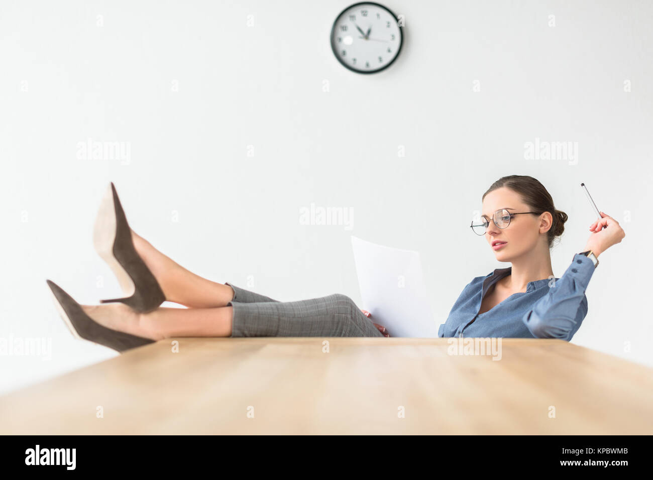 Businesswoman sitting with legs on table - Stock Image