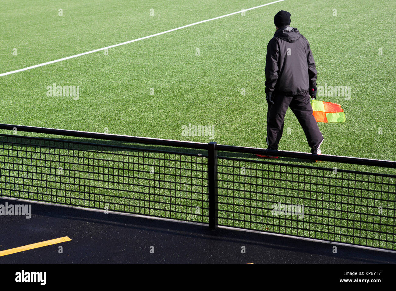 A match official, the linesman, walking along the edge of a new artifical grass pitch carrying his flag. - Stock Image