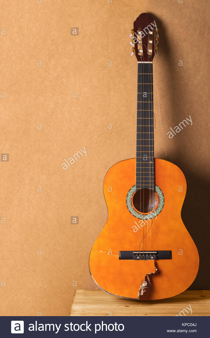 Full length front view of a broken classical guitar with dust and small debris on a wooden background. Stock Photo
