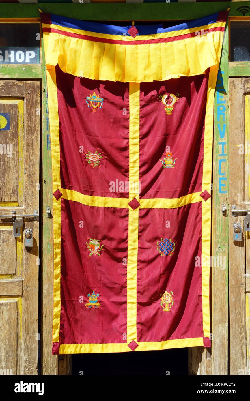 Door curtain with the 8 auspicious Tibetan Buddhist symbols, Lo Mantang, Upper Mustang region, Nepal. - Stock Image