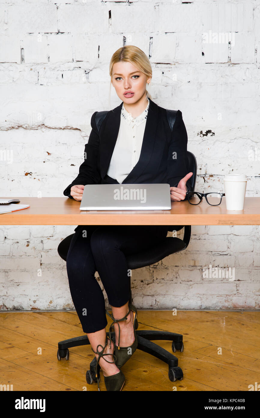 3f8e5abf777 Young blond beauty businesswoman sitting at a office table with laptop