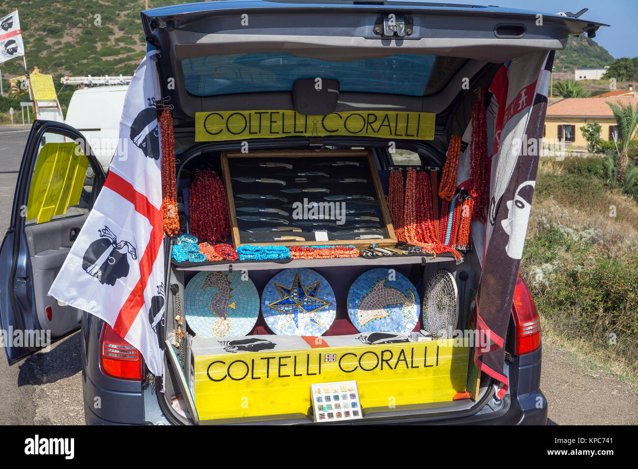 Travelling salesman with shop in car boot offers knifes and neckless made of red corals, Castelsardo, Sardinia island, - Stock Image