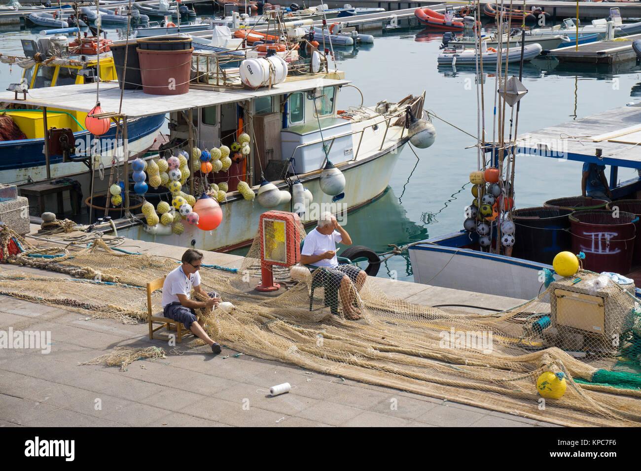 Fishermen repairing nets at the harbour of Isola Rossa, Olbia-Tempio, Sardinia, Italy, Mediterranean  sea, Europe - Stock Image