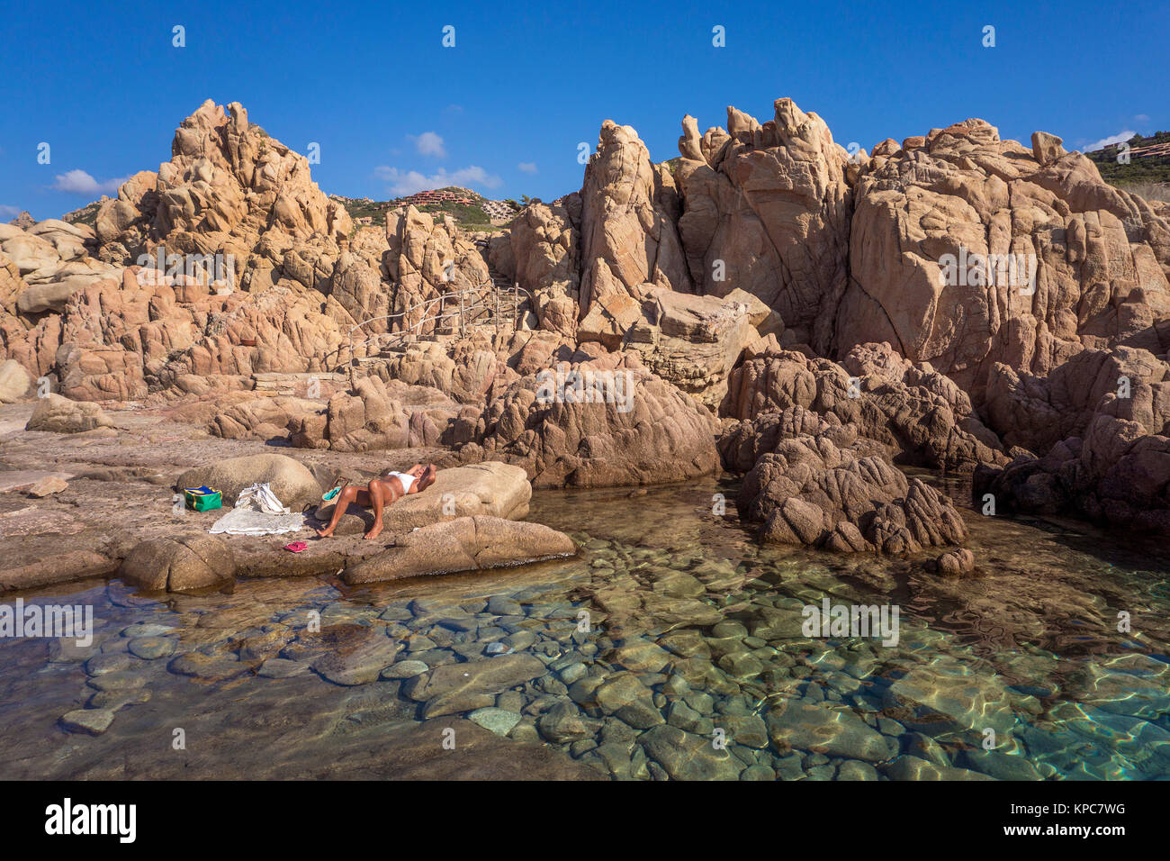 Woman takes a sunbath at the Idyllic rocky coast of Costa Paradiso, Porphyry rocks, Sardinia, Italy, Mediterranean - Stock Image