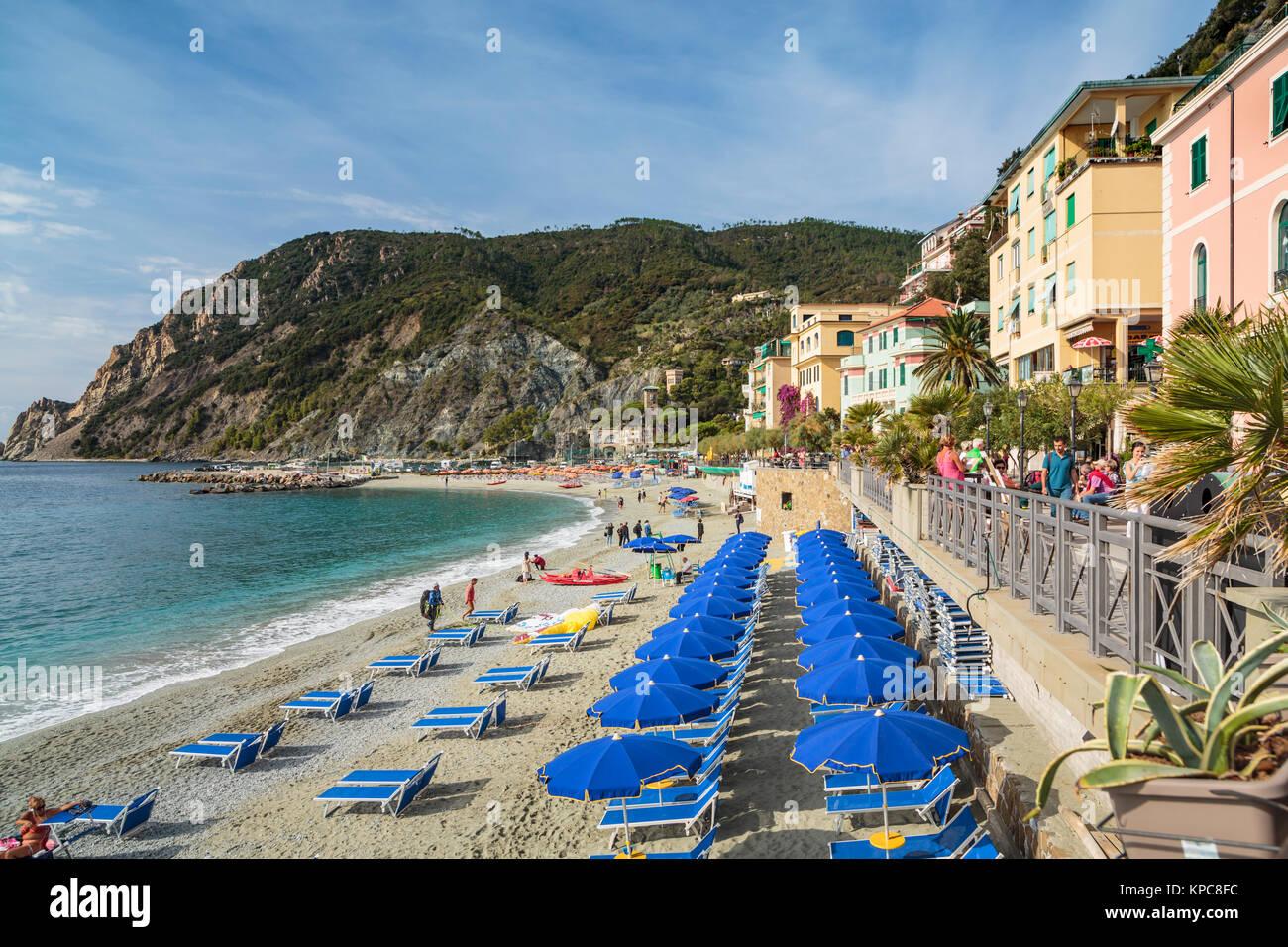 The sandy beach with blue umbrellas in Monterosso al Mare, Liguria, Italy, Europe. - Stock Image