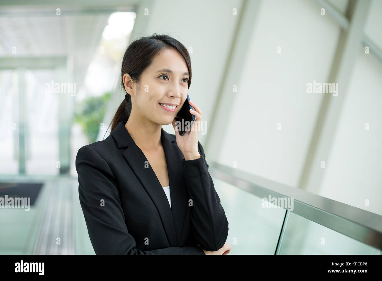 Asian Businesswoman talk to mobile phone at office - Stock Image