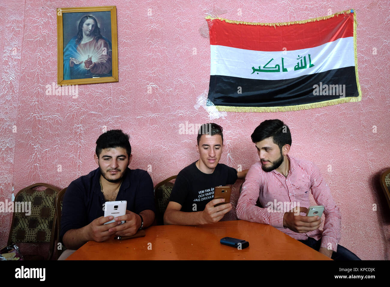 Iraqi flag and an image of Jesus Christ on a wall in an newly opened tearoom in the IS-liberated city of Karakosh, - Stock Image
