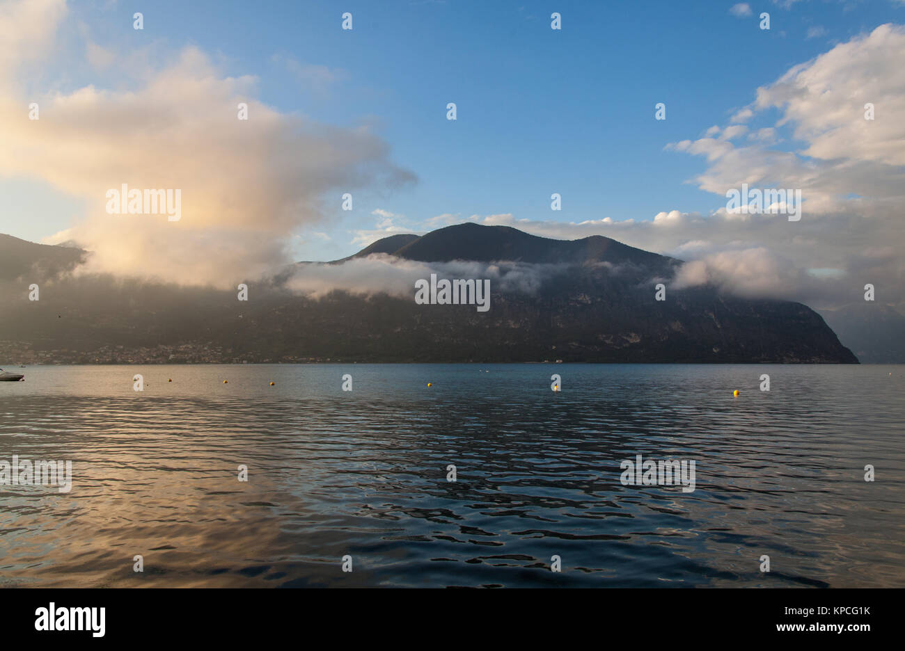 Lake Iseo, Italy. Picturesque dusk view of Lake Iseo, with the Predore peninsula in the background. The scene was - Stock Image