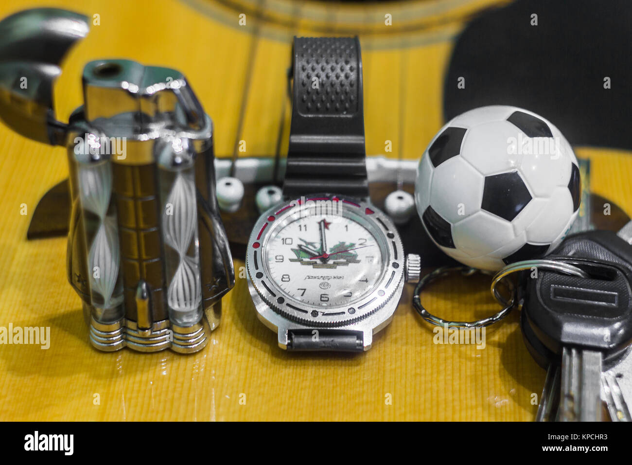 Wrist watch, cigarette, lighter, keychain with keys and acoustic guitar in the background - Stock Image