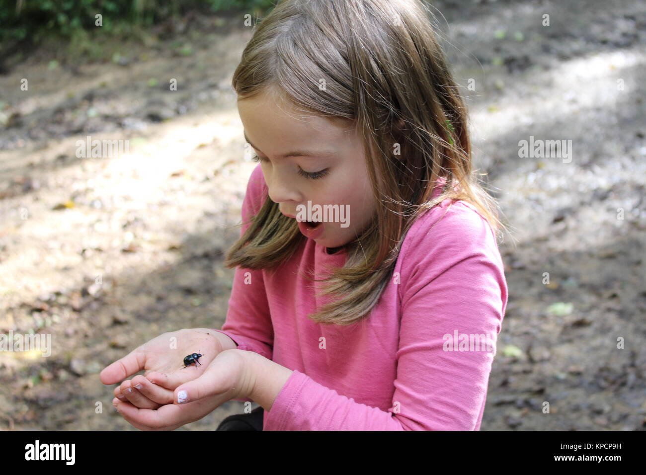 girl holding a beetle - Stock Image