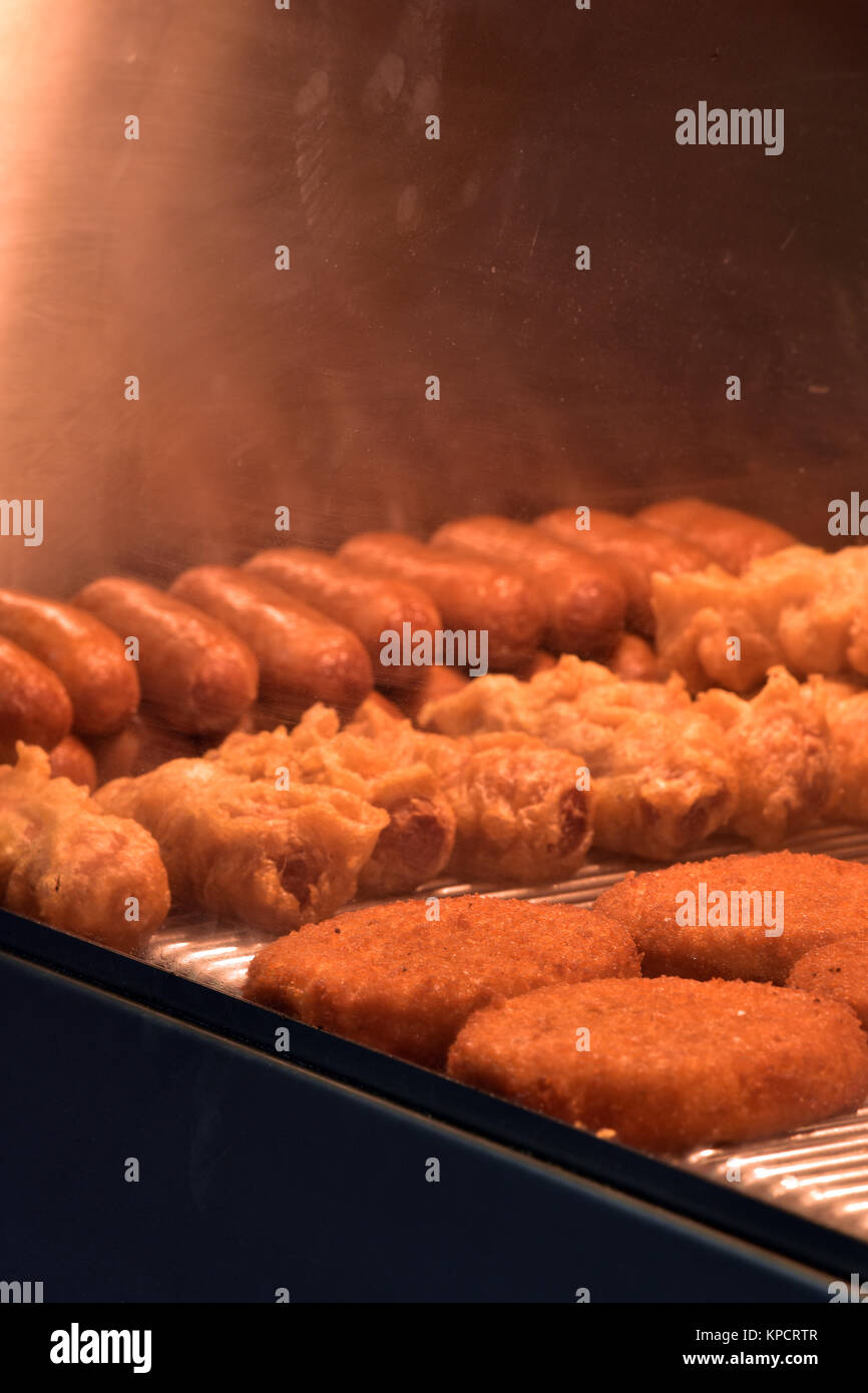 Fried food plain and battered sausages and fish cakes in a heated counter or warmer in a fish and chip or fast food - Stock Image