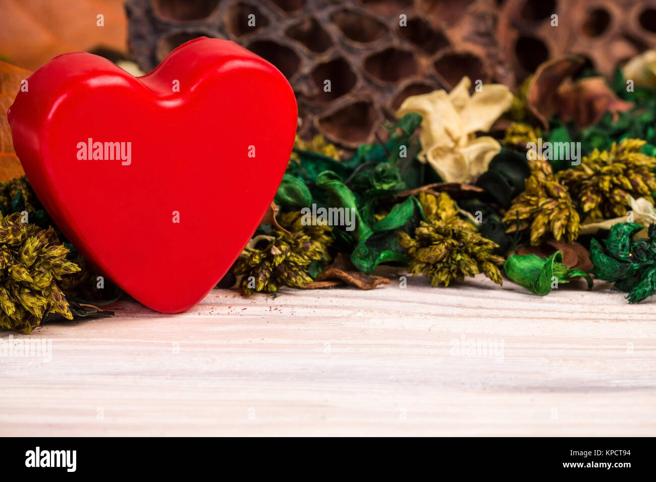 Cool background with dried plants flowers and red heart - Stock Image