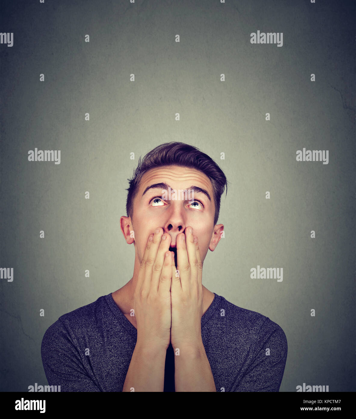 Young man covering mouth looking helplessly up and scared of things to come. - Stock Image