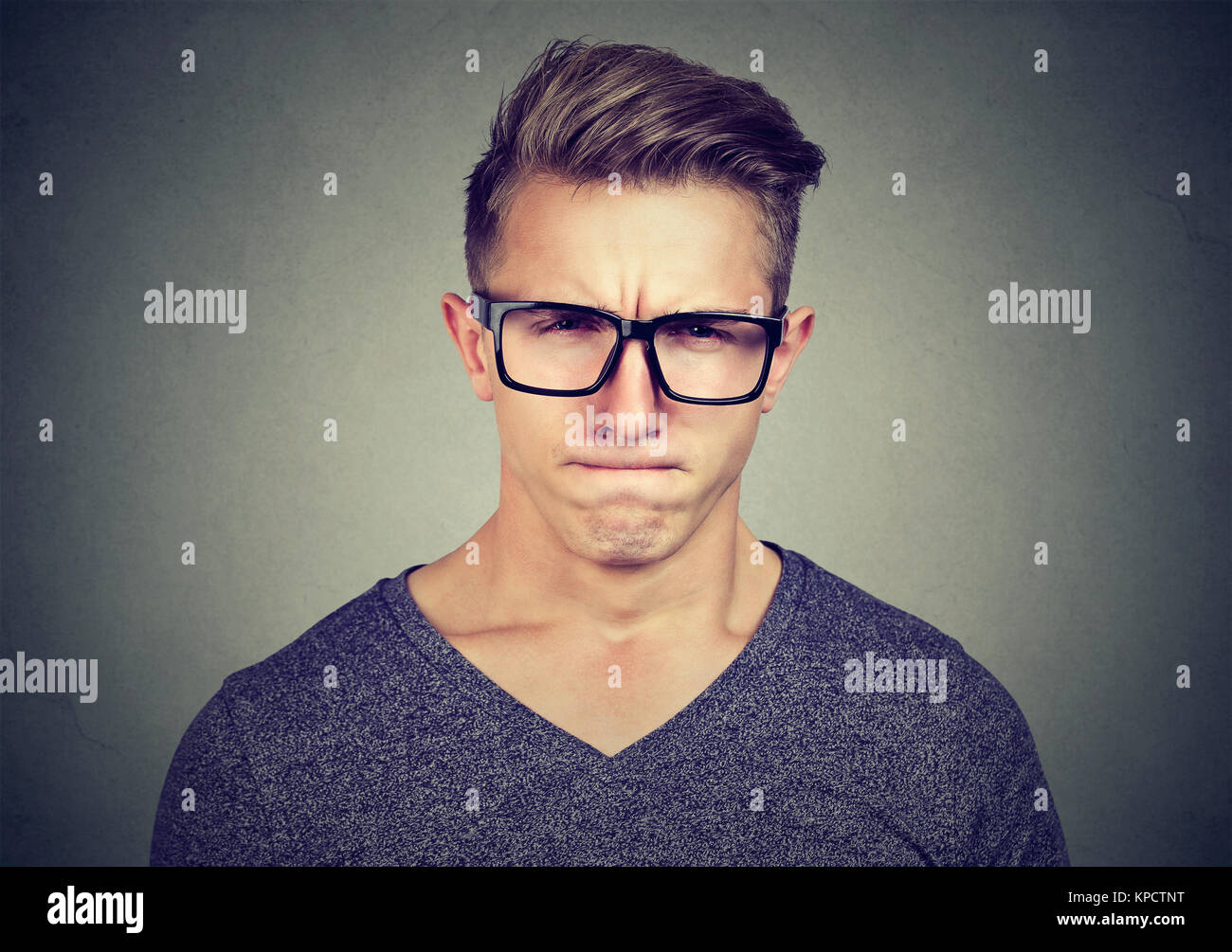 Young expressive man in black eyeglasses looking at camera with expression of total disbelief and frustration - Stock Image