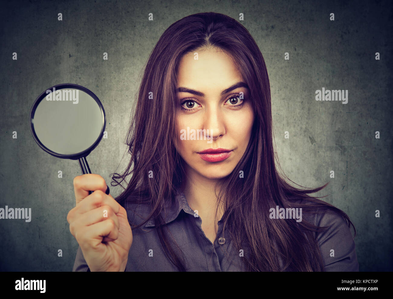 Young determined model holding magnifier and looking seriously at camera. - Stock Image