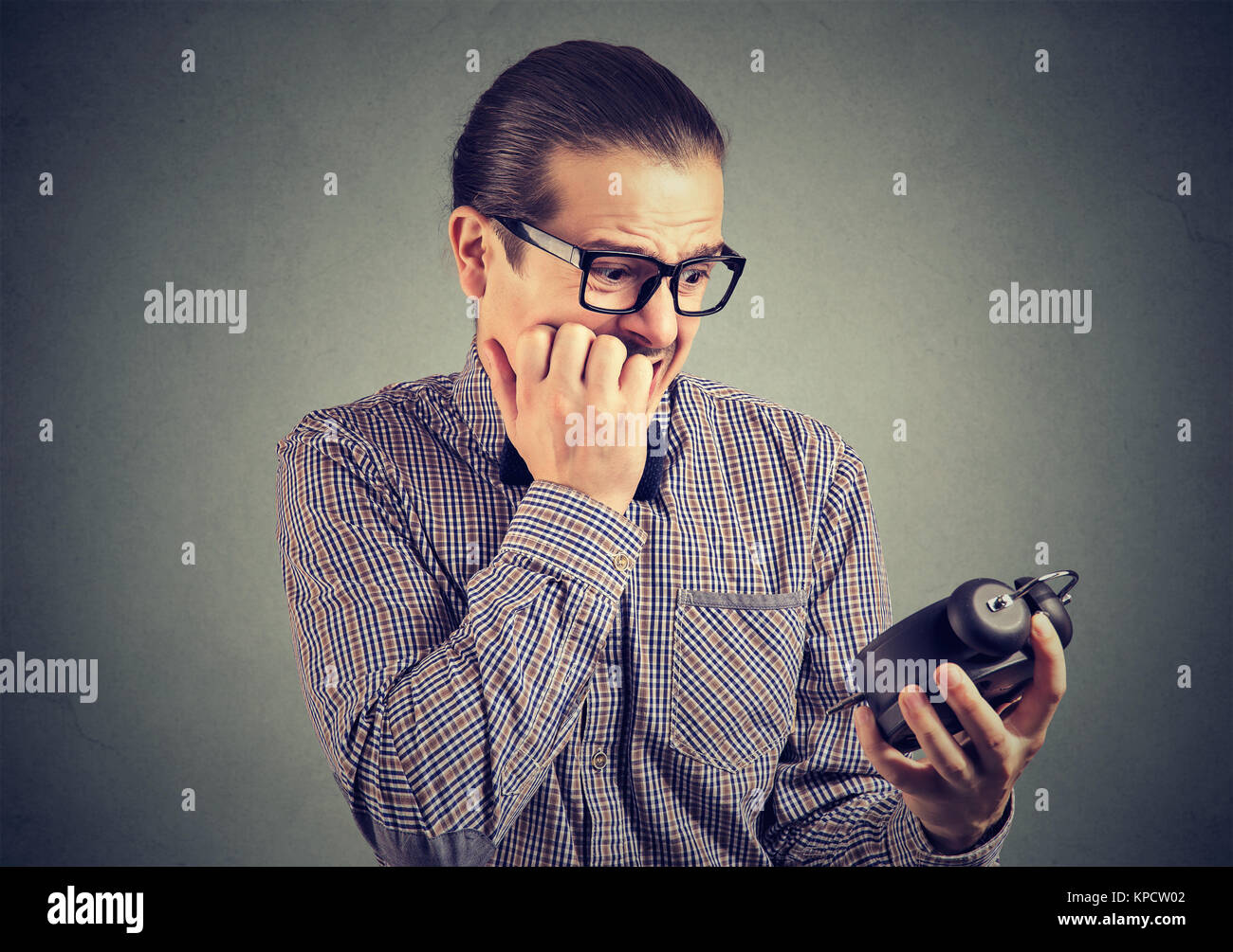 Young man in eyeglasses looking nervously at clock feeling pressure of lack of time. - Stock Image