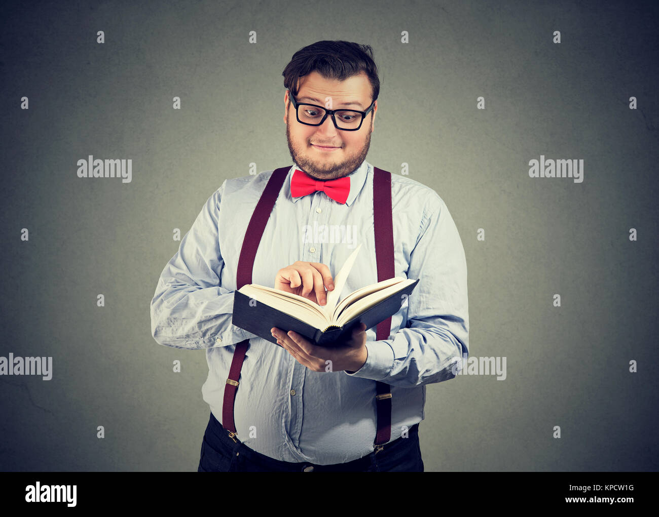 Content man in eyeglasses reading interesting book looking slightly astonished. - Stock Image