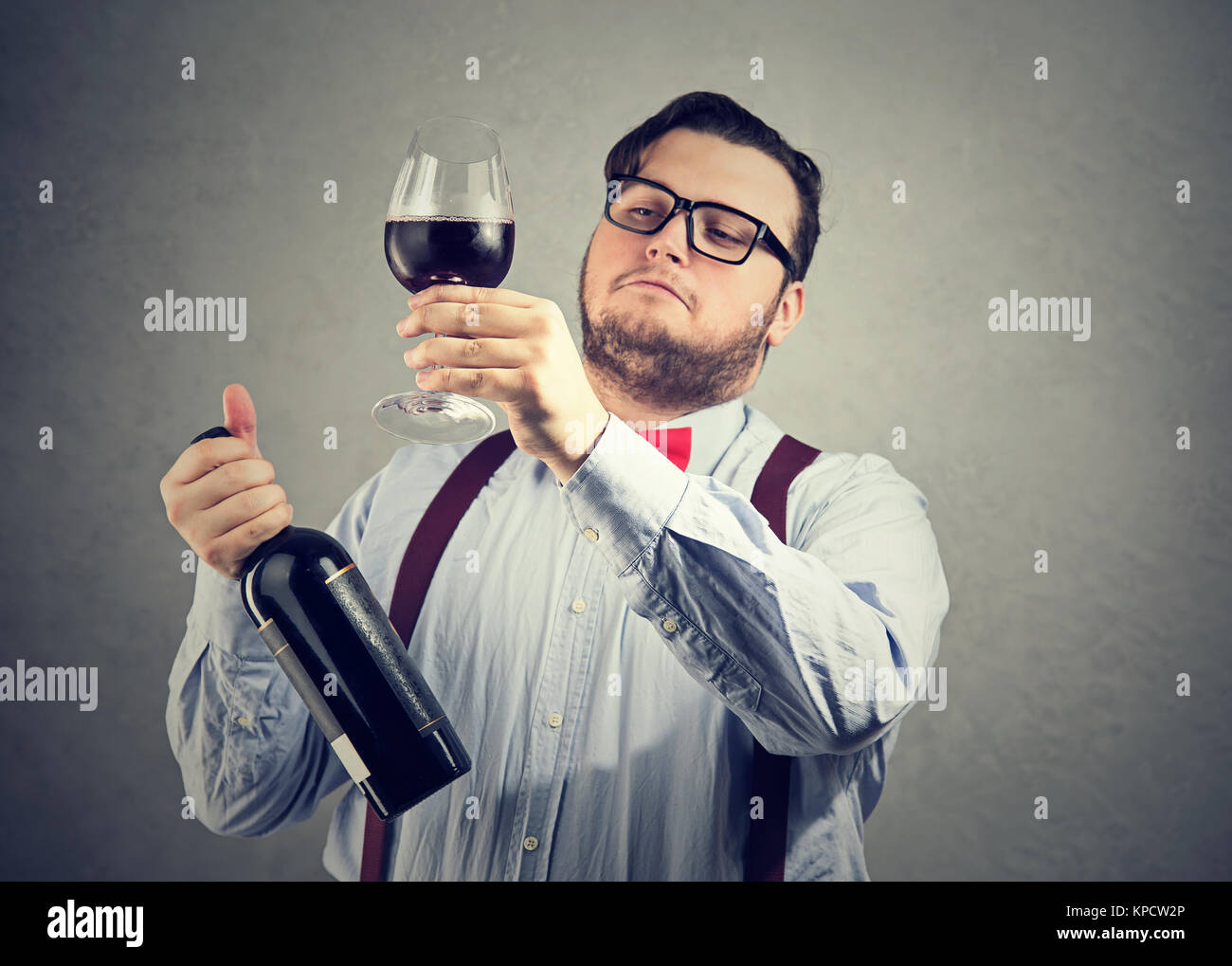Chubby man in wearing eyeglasses and bow tie holding wineglass and judging drink quality looking overconfident. - Stock Image