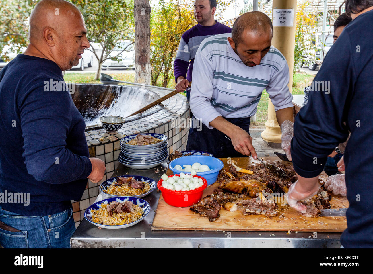 Men Cooking and Serving PLOV (The National Dish) At The Central Asian Plov Centre, Tashkent, Uzbekistan - Stock Image