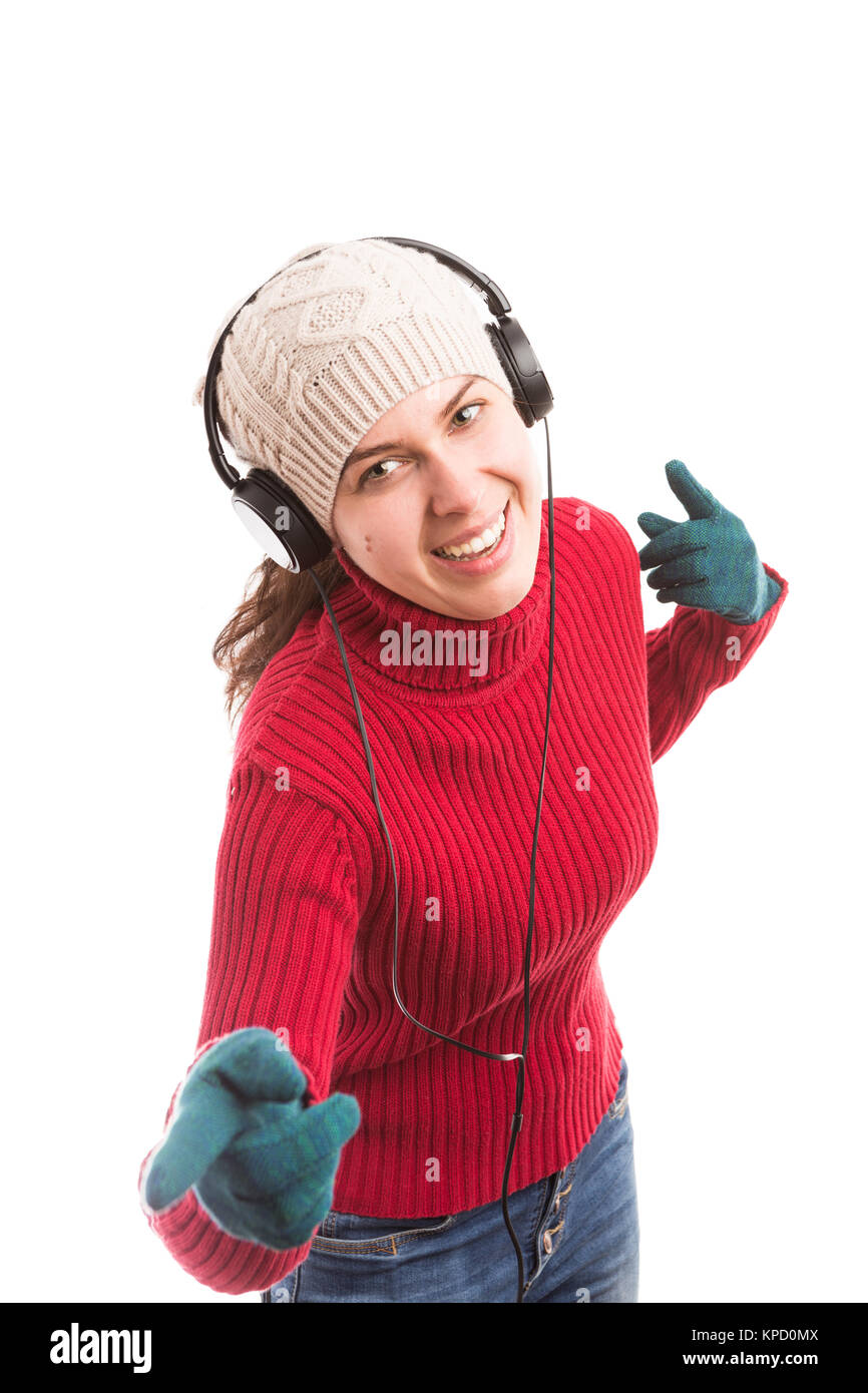 Young woman listening musing and dancing happy wearing fashionable winter clothes - Stock Image