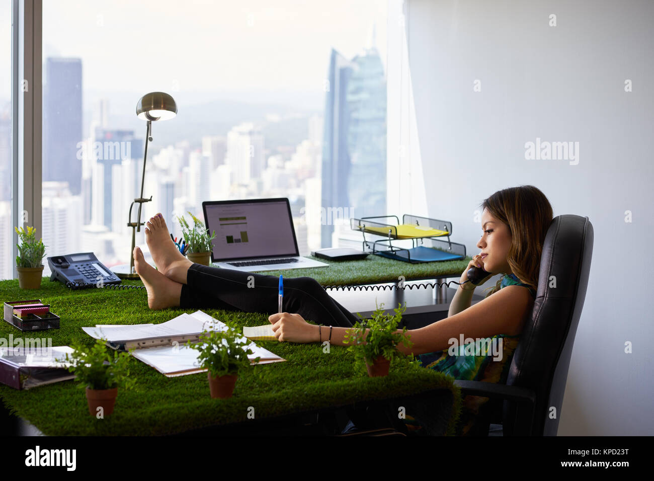 Environmentalist Woman Writes Note Barefeet On Office Desk - Stock Image
