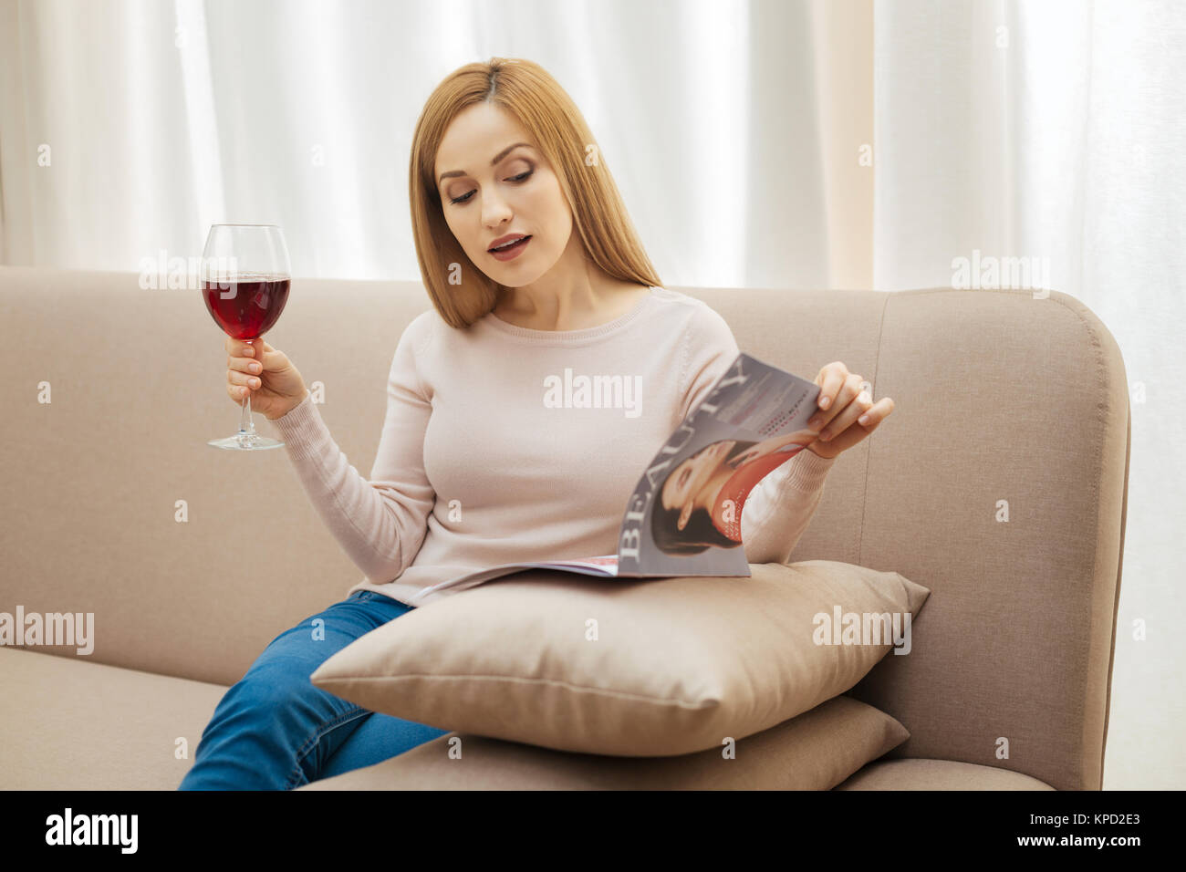 Beautiful woman with a glass of wine and magazine - Stock Image
