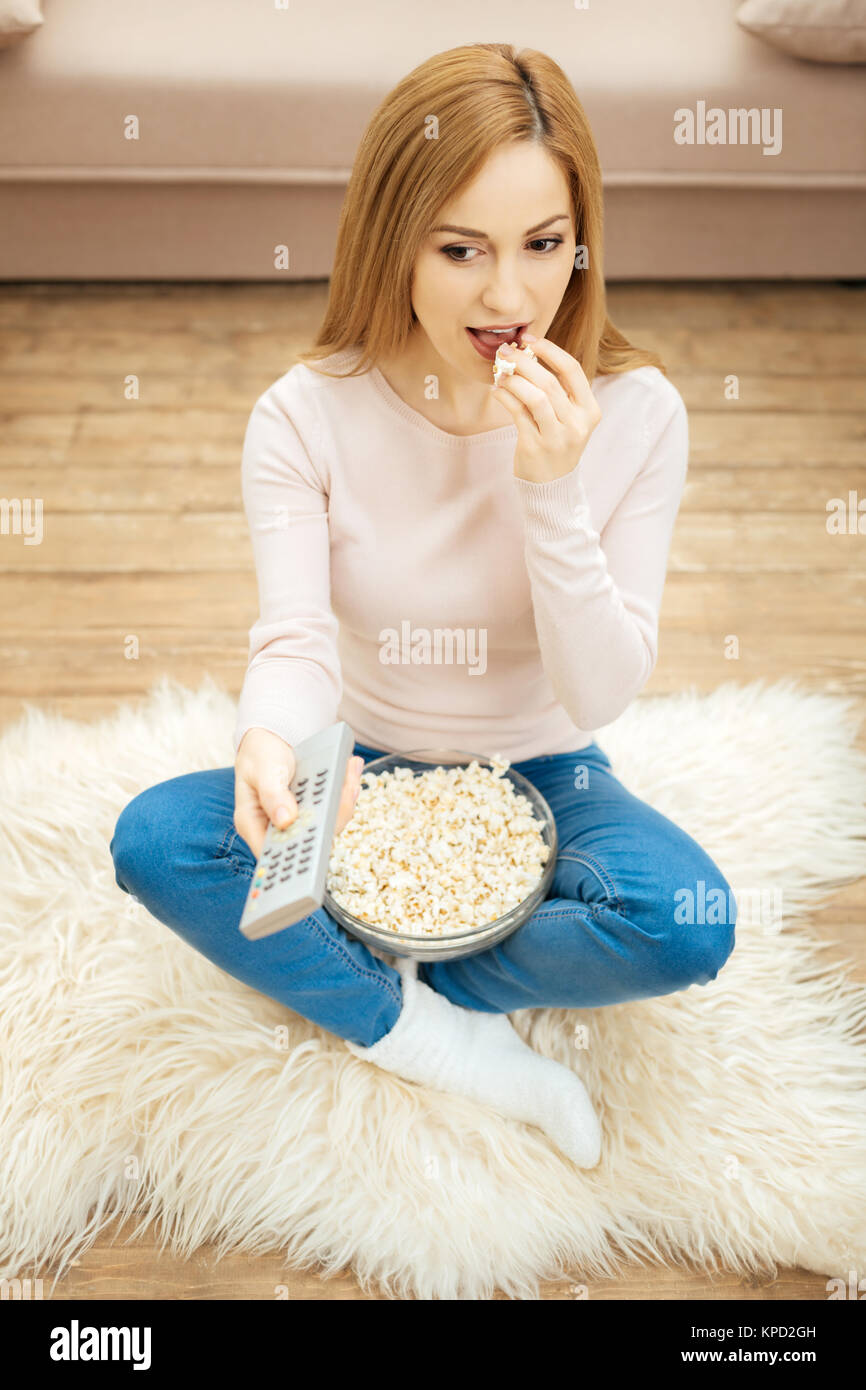 Joyful woman in jeans eating popcorn on the floor Stock Photo