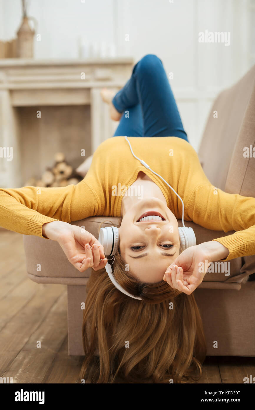 Exuberant smiling woman listening to music - Stock Image