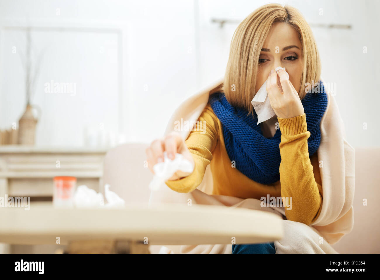 Ill lady feeling bad and sitting on the couch - Stock Image