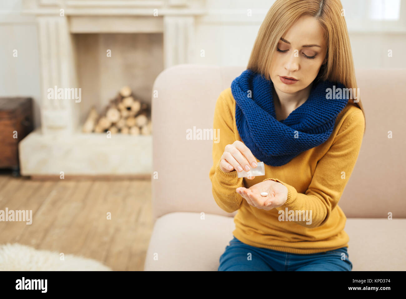 Unwell blond woman taking pills - Stock Image
