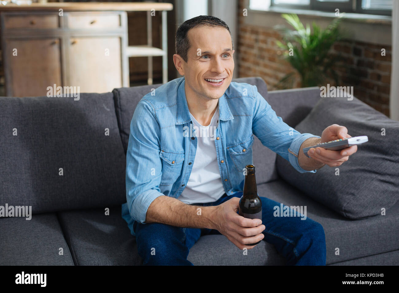 Cheerful male person watching TV - Stock Image