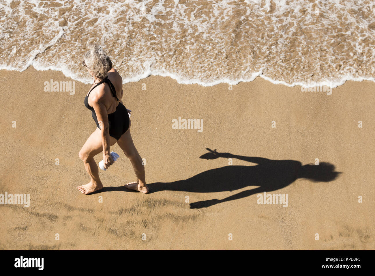 Mature woman in swimming costume walking on beach in Spain - Stock Image