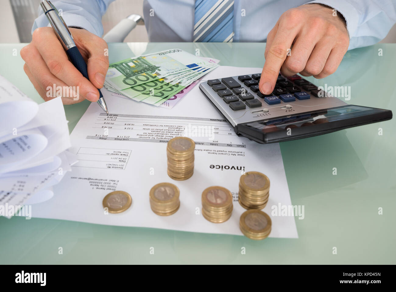 Businessman Calculating Invoice With Money At Desk Stock Photo