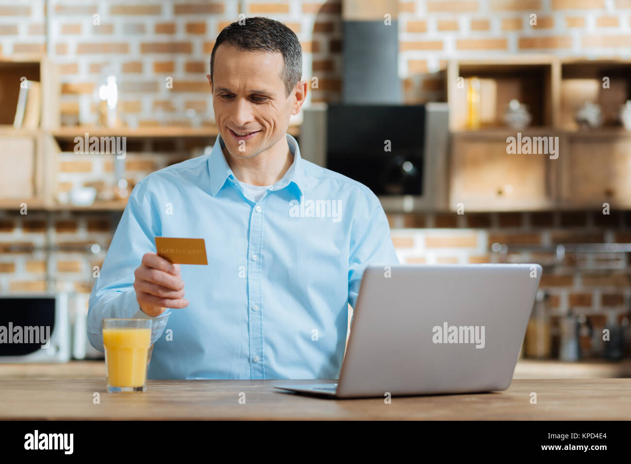 Attentive modern male that looking at his card - Stock Image