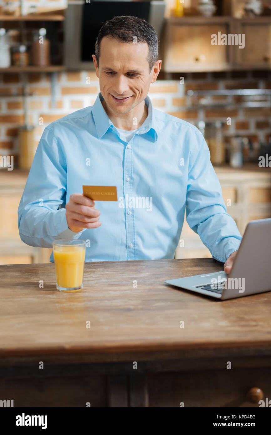 Attractive brunette male checking his account - Stock Image
