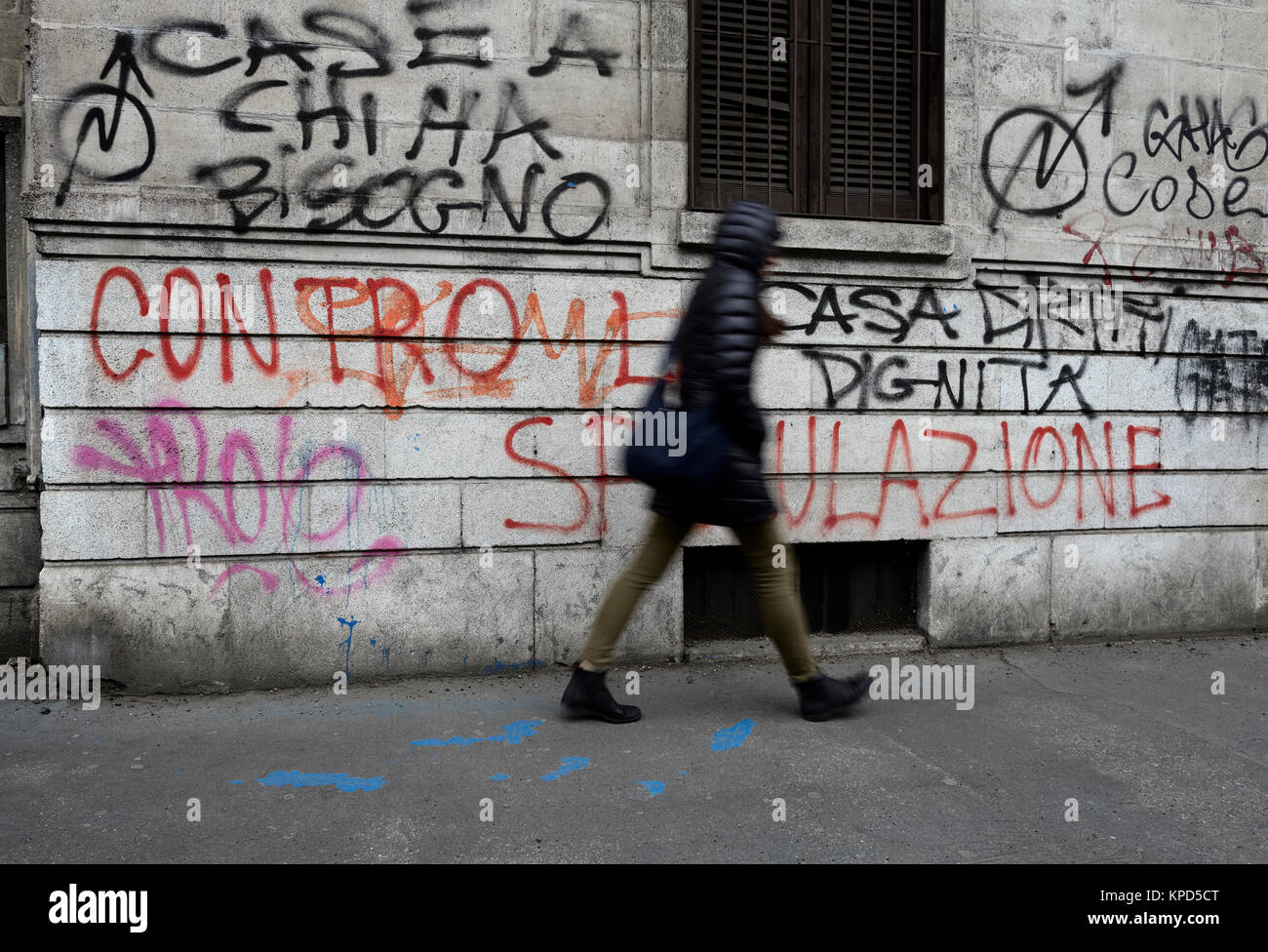 Woman walks near a wall with political writings - Stock Image