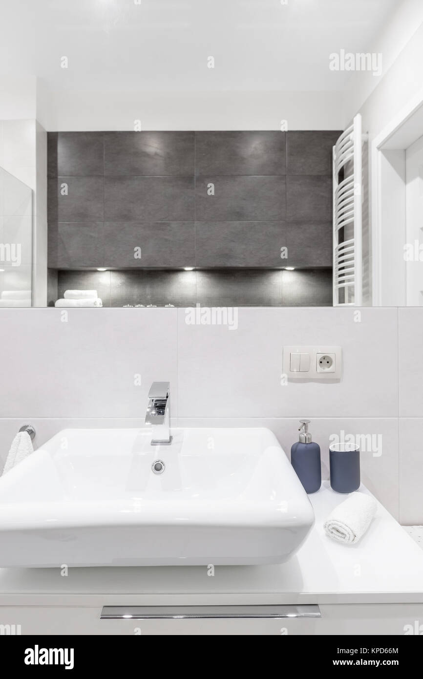 White sink and mirror in modern bathroom with concrete tiles Stock ...