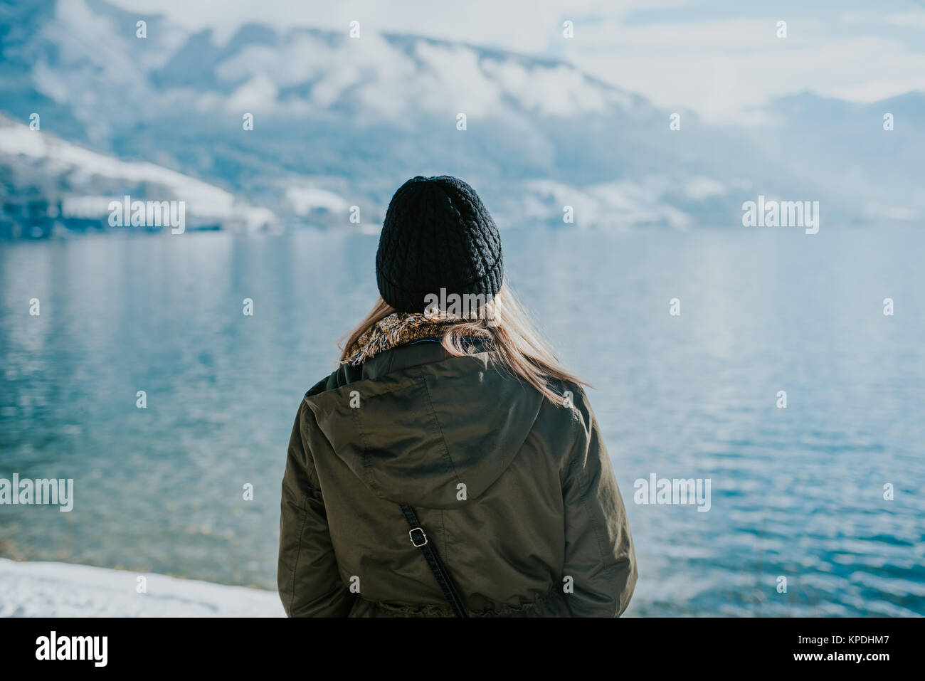 Woman standing on the lakeshore with snowy mountains in the background - Stock Image
