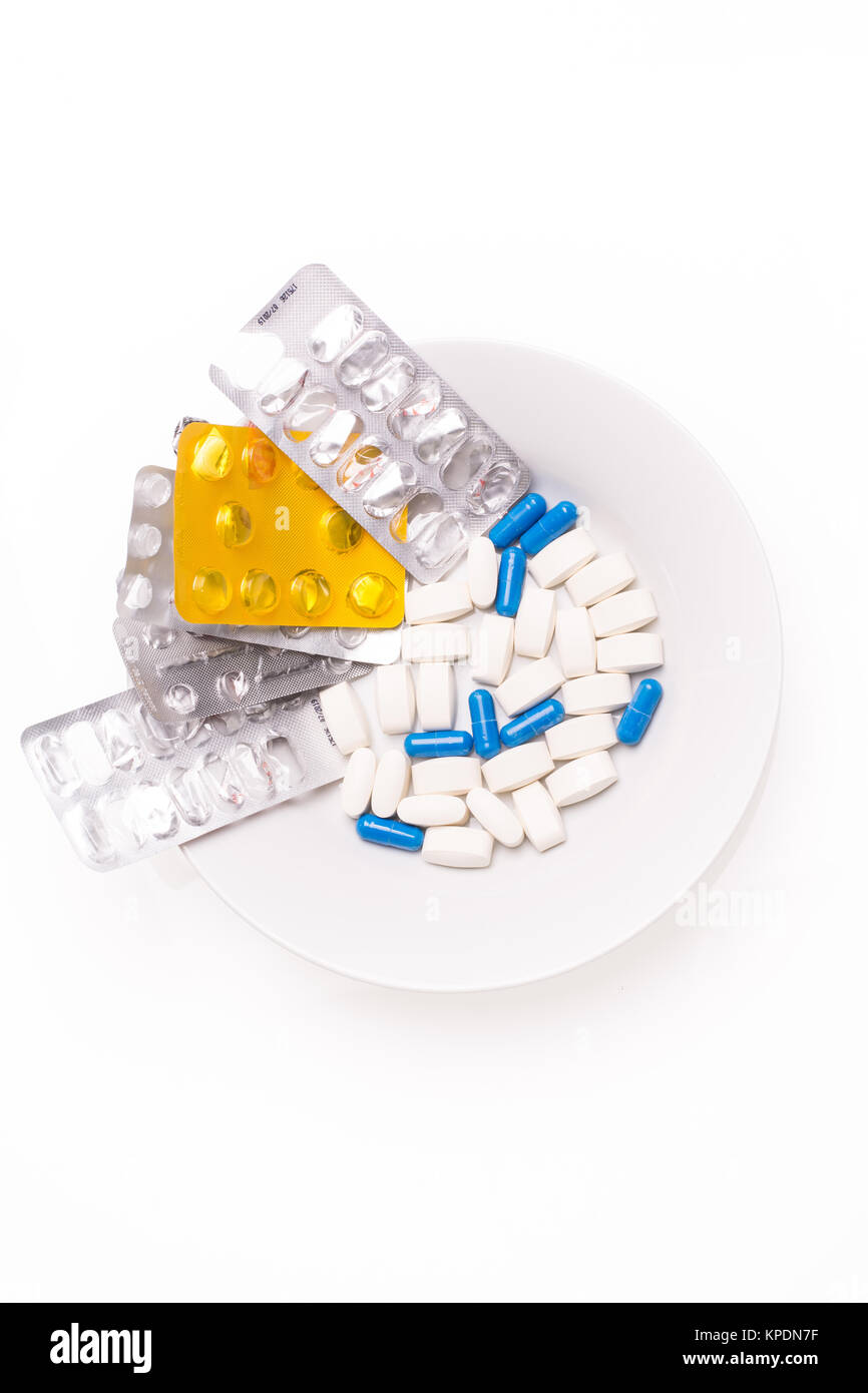 Plate with white and blue medical pills for treating diseases - Stock Image