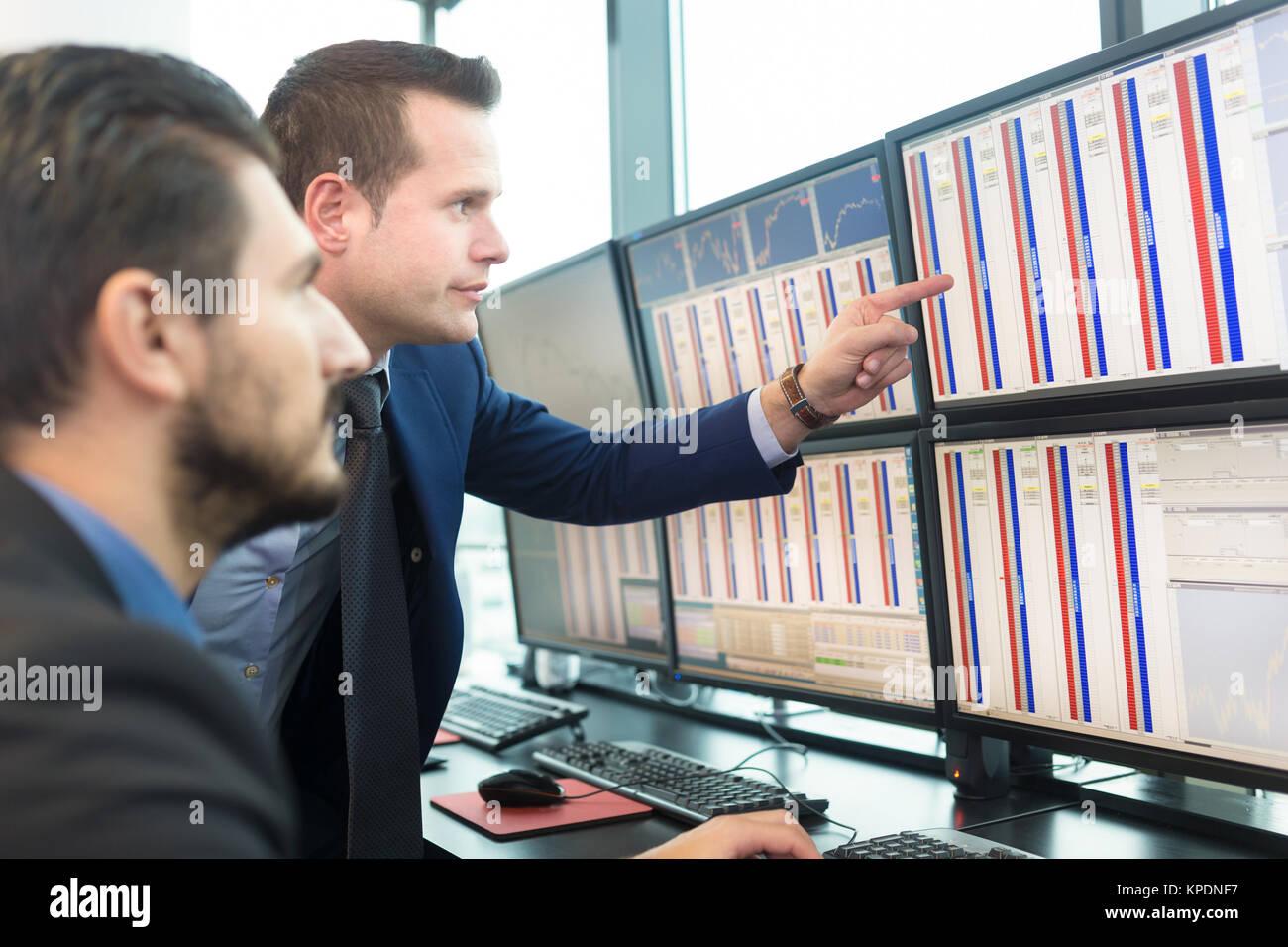 Stock traders looking at computer screens. - Stock Image