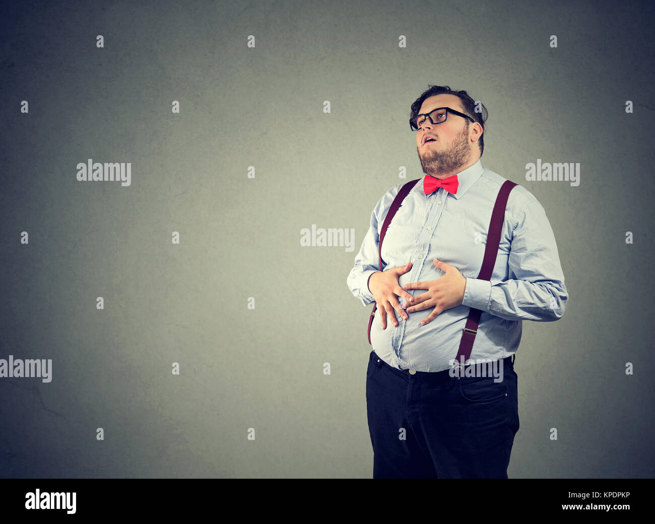 Irritated man with overweight wearing glasses and formal clothing having digestive trouble. - Stock Image