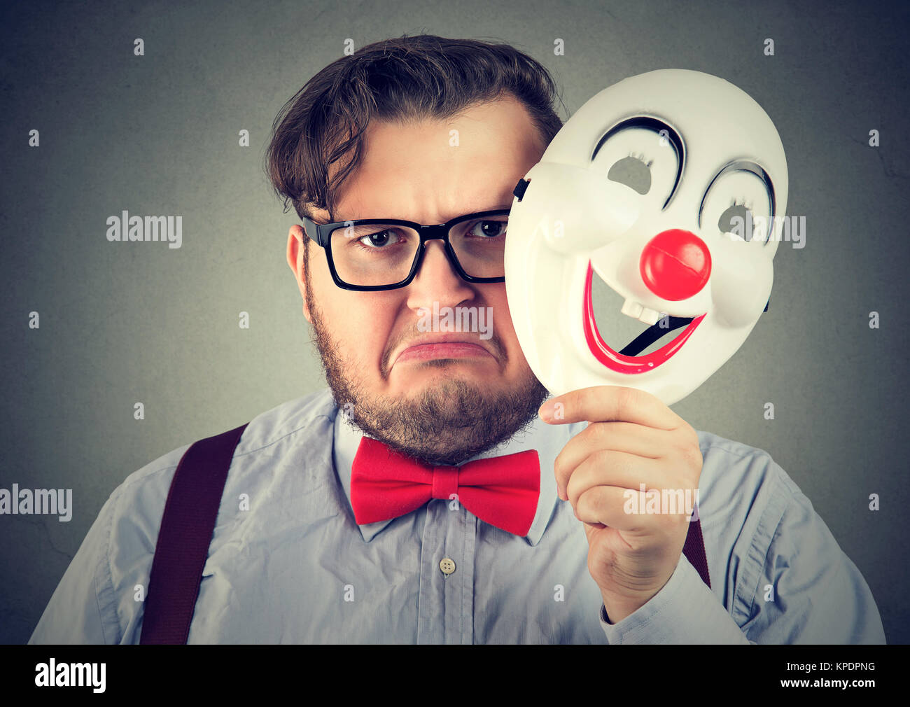 Young upset man frowning while looking at camera and holding happy clown mask. - Stock Image