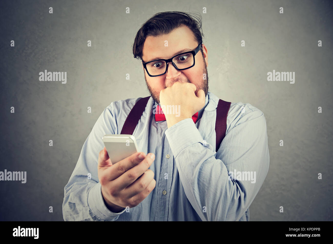 Chubby man in bow-tie looking anxious while watching smartphone and having bad news. - Stock Image