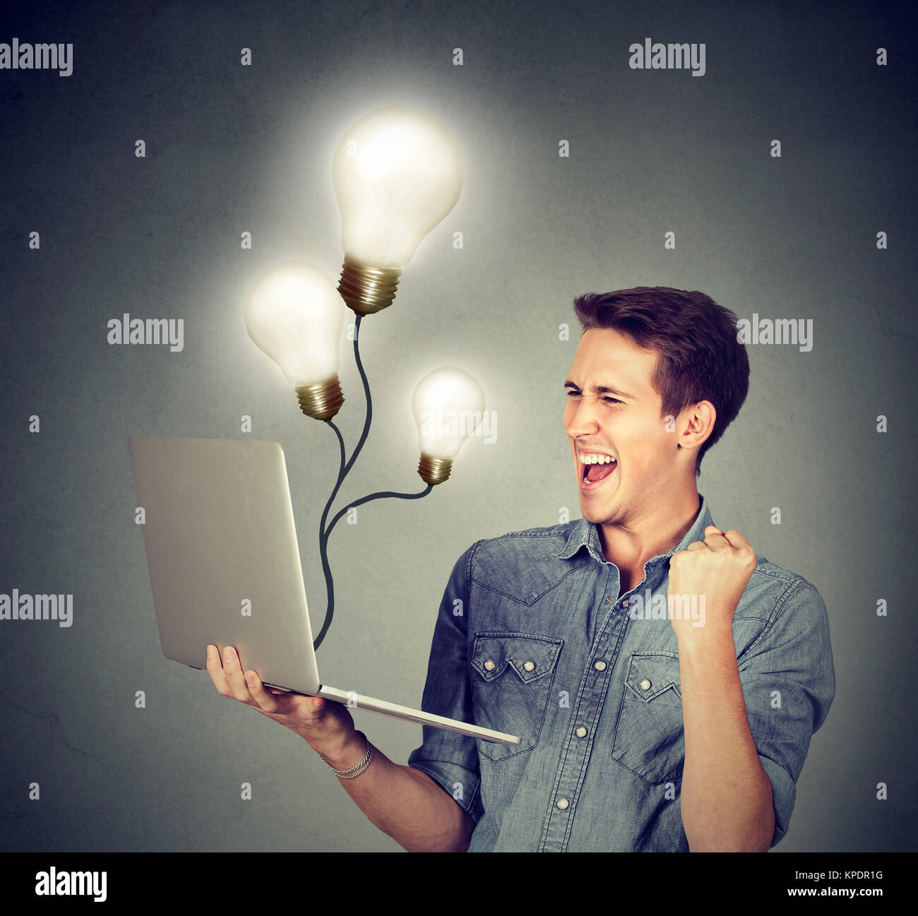 Young man holding laptop and celebrating success of great ideas. - Stock Image