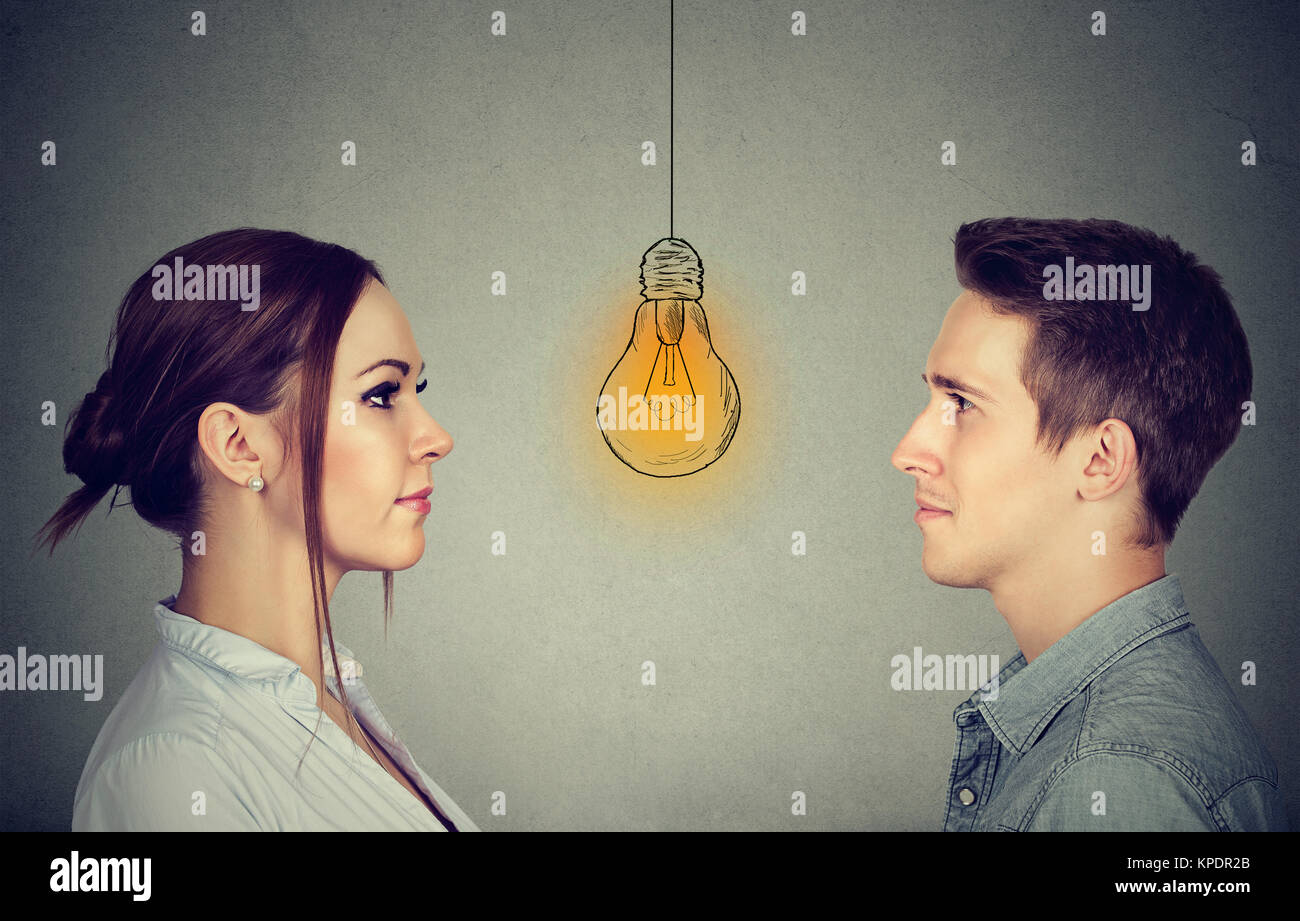 Cognitive skills ability concept, male vs female. Man and woman looking at bright light bulb - Stock Image