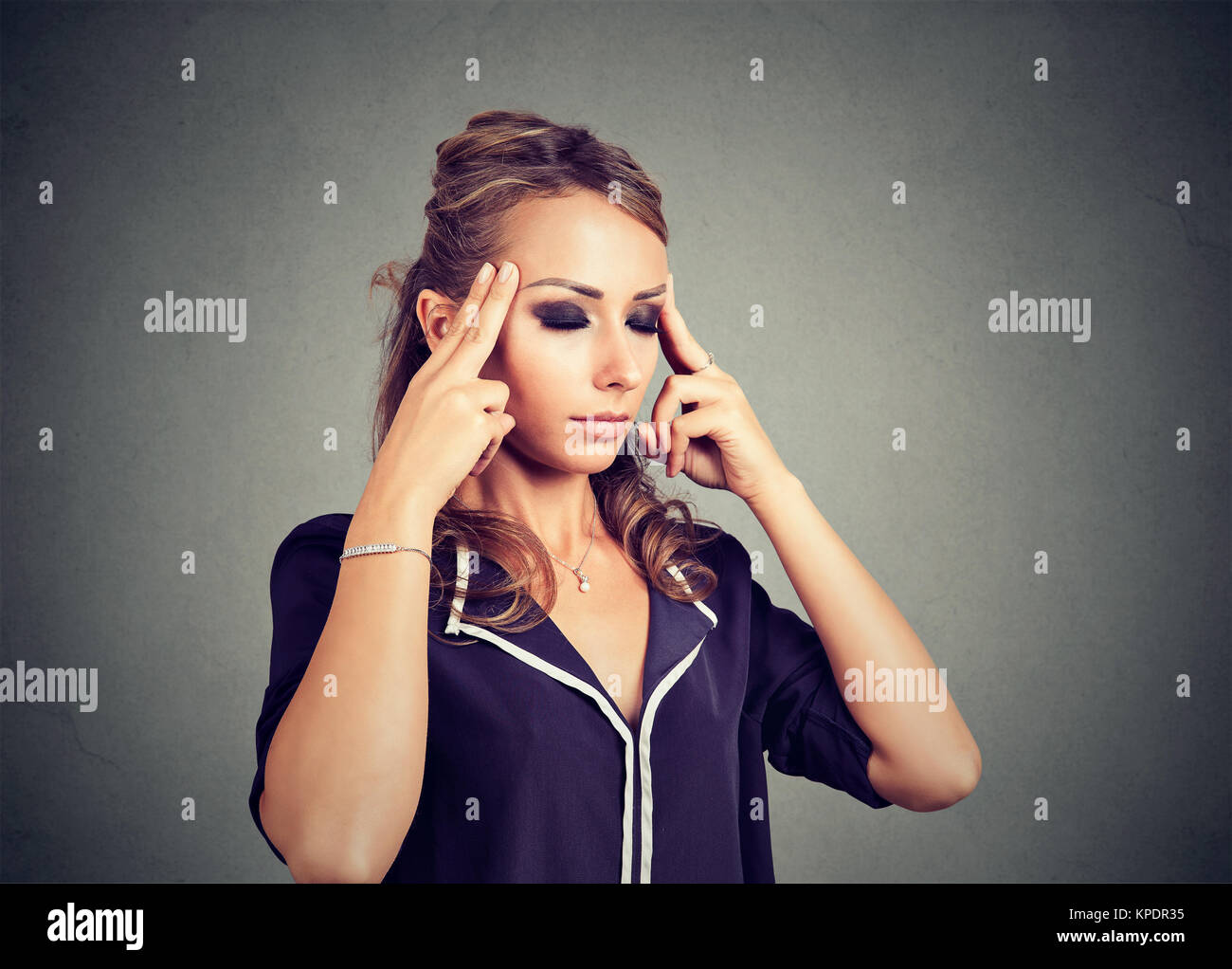 Young concentrated woman rubbing temples looking exhausted and overwhelmed. - Stock Image