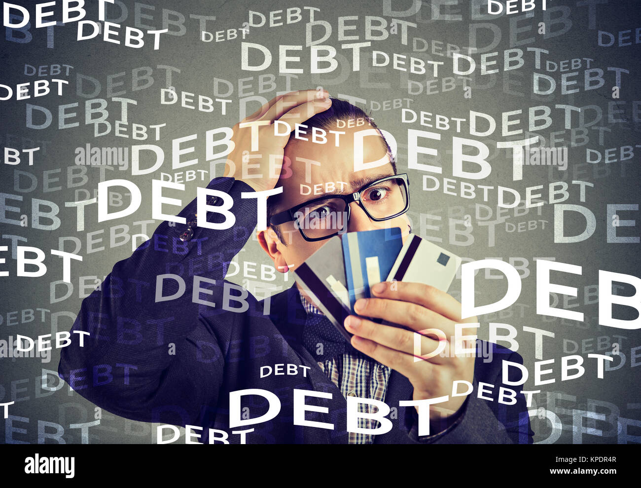 Concerned man looking at few credit card scared with huge amount of debt. - Stock Image